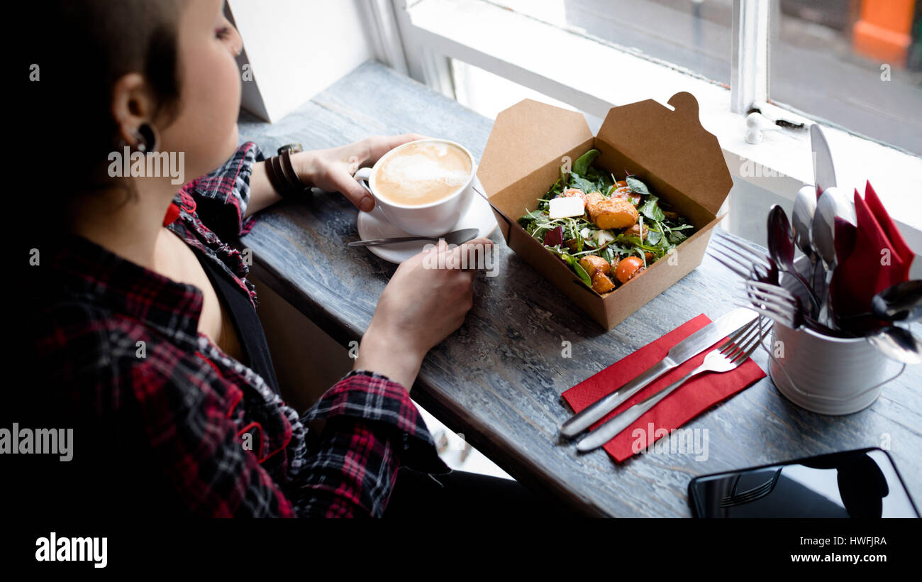 Beautiful woman having coffee and salad in café - Stock Image