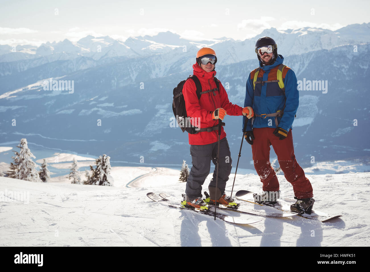Two skiers standing together on snow covered mountain during winter Stock Photo