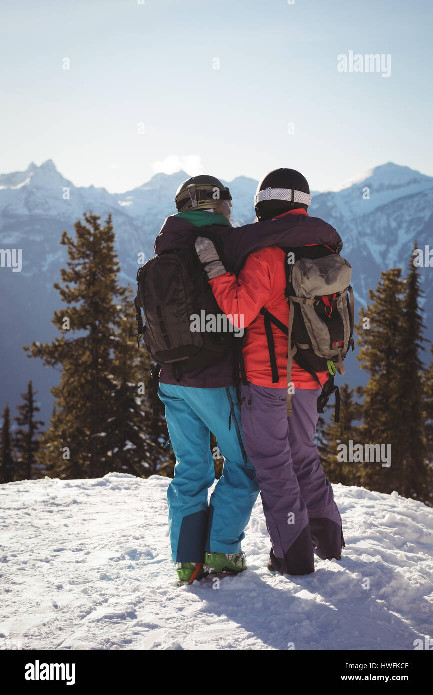 Rear view of two skiers standing together with arm around on snow covered mountain Stock Photo
