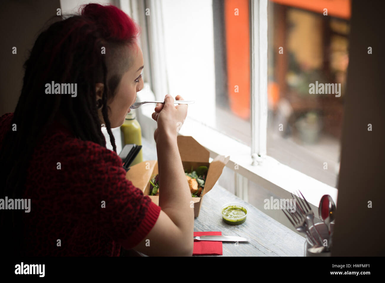 Woman looking through window while having a salad in café - Stock Image