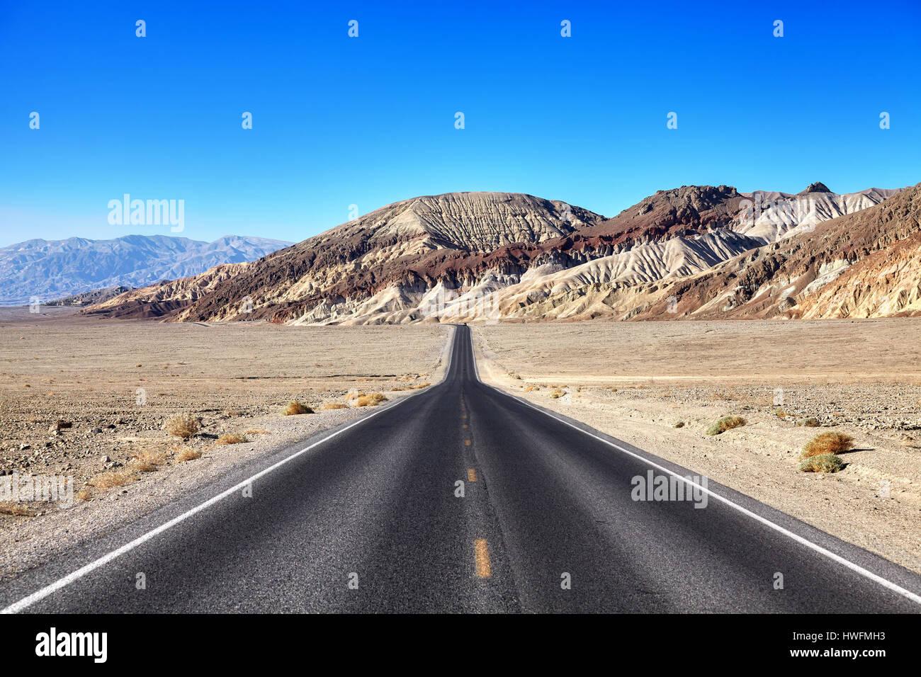 Desert road towards mountain range at Death Valley, travel concept, focus on mountains, USA. - Stock Image