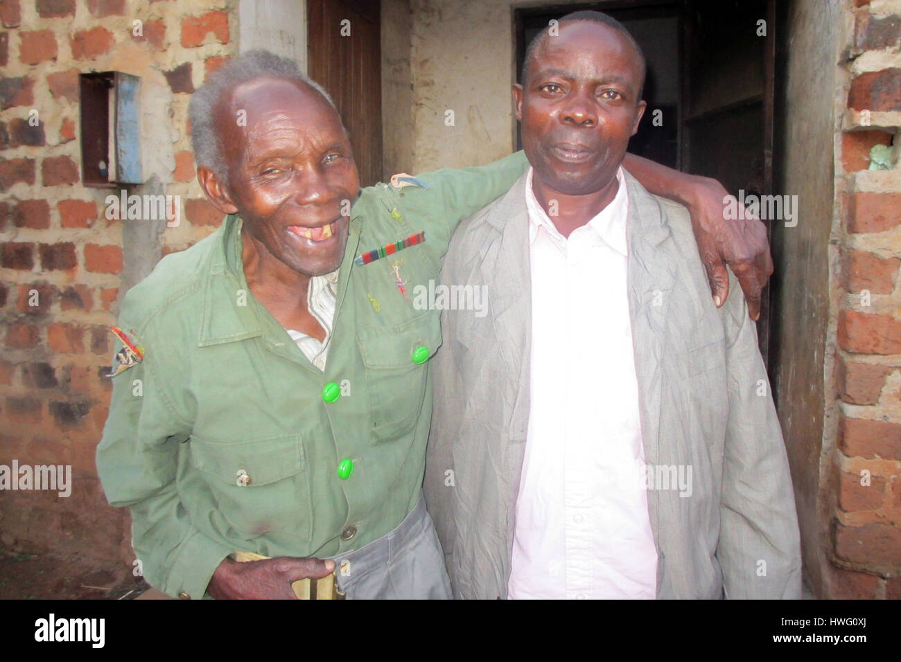 World War II veteran Elismus Katende (l), wearing his old uniform, shares a lugh with his grandson in Mugomba village, - Stock Image