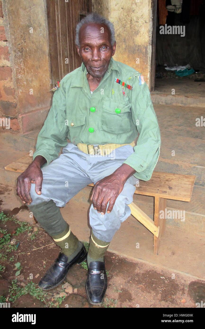 World War II veteran Elismus Katende wears his old uniform in Mugomba village, Uganda, on February 21, 2017. Ugandan - Stock Image
