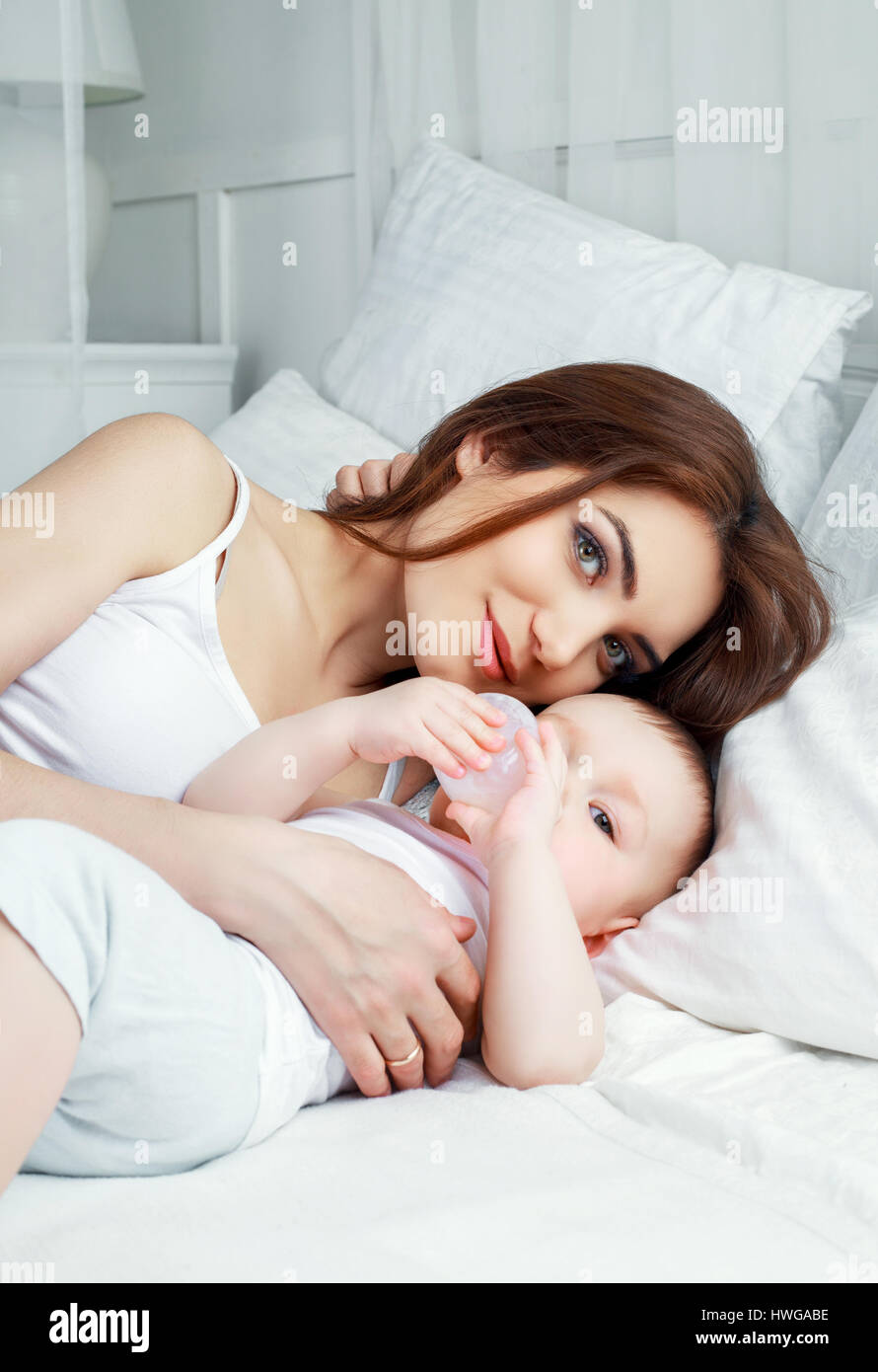 happy beautiful mother with her one year old son in bed at home - Stock Image