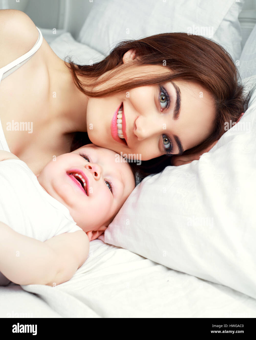 happy beautiful mother with her one year old son in bed at home Stock Photo