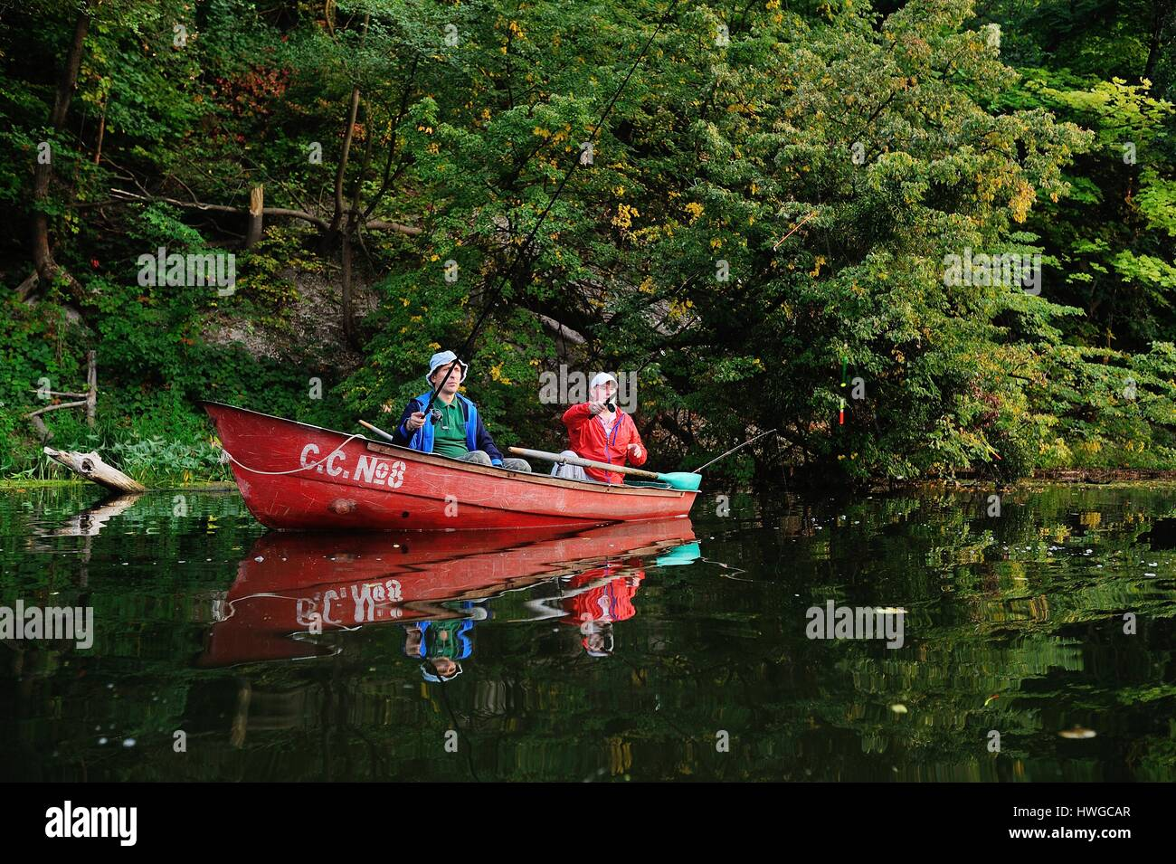 Two fishermen in a boat with fishing rods catching fish - Stock Image