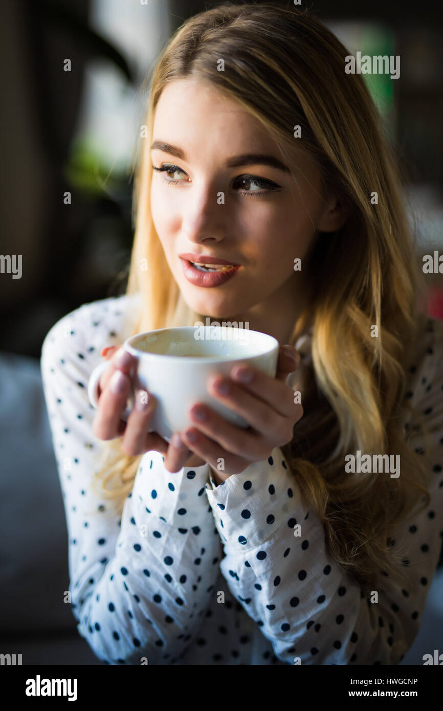 Portrait of young gorgeous female drinking tea and thoughtfully looking out of the coffee shop window while enjoying - Stock Image