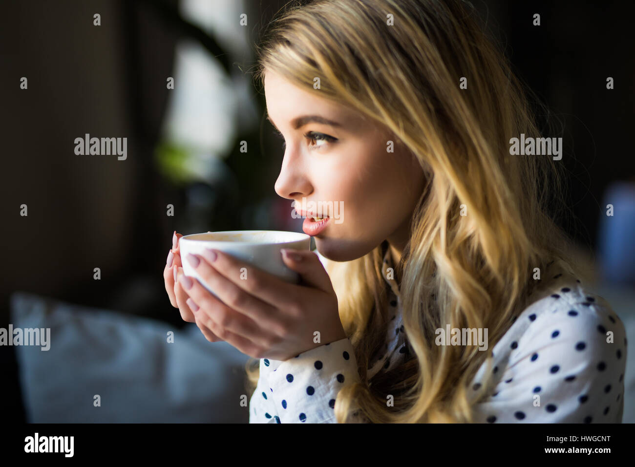 Portrait of young gorgeous female drinking tea and thoughtfully looking out of the coffee shop window while enjoying Stock Photo