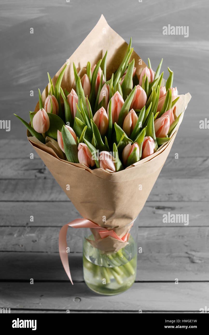 c8406238b2800 bouquet of pink tulips in a package of kraft paper, on gray wodden  background