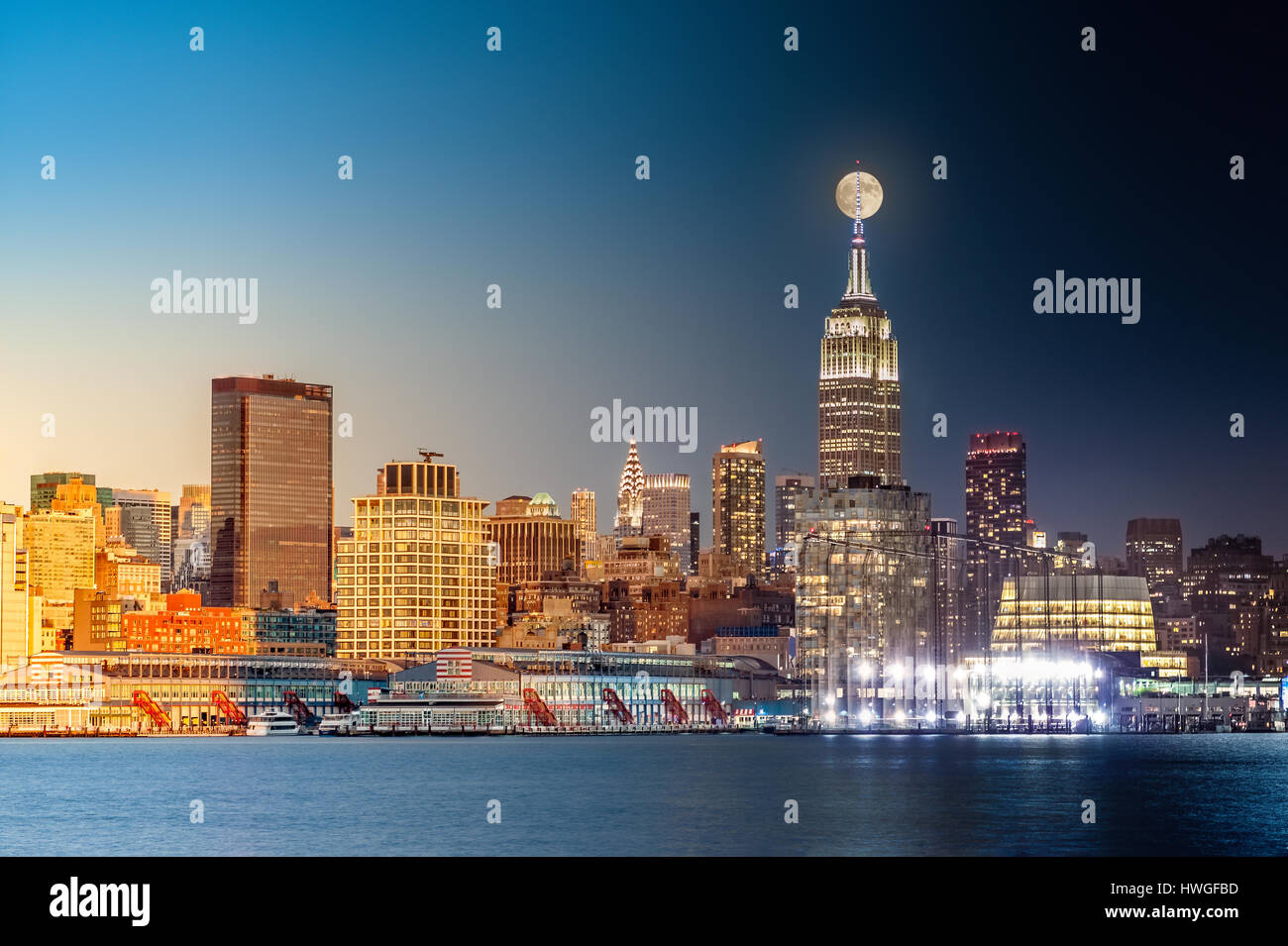 Composite day to night timelapse with the full moon rising above New York City skyline. - Stock Image
