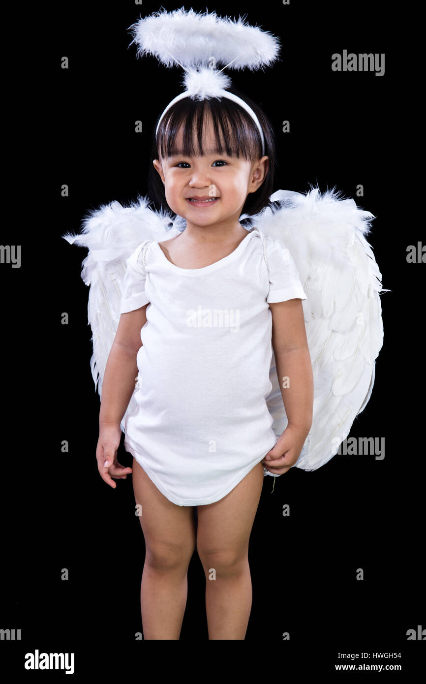 Smiling Asian Chinese Little Angel in dark black isolated studio background.