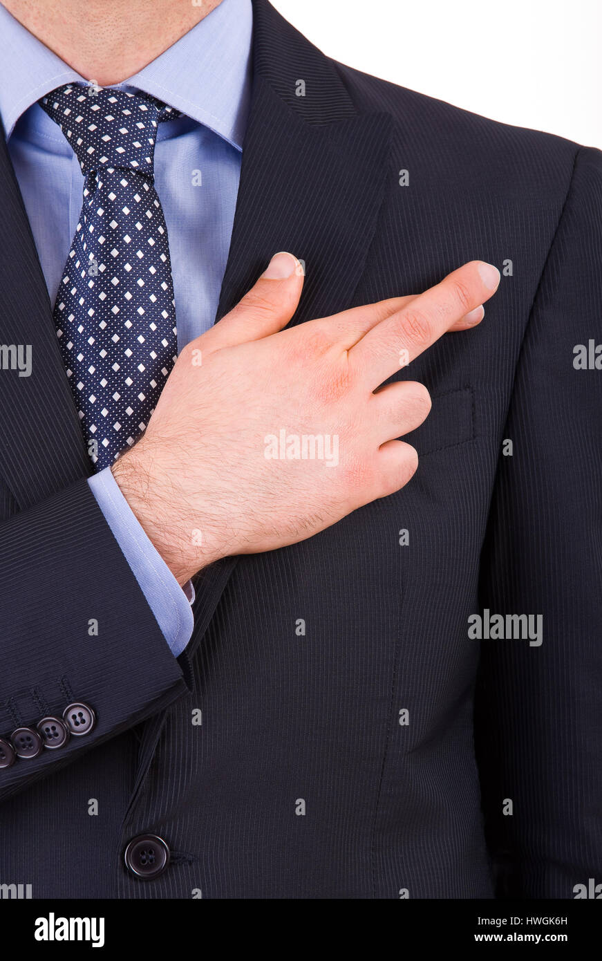 Business man with fingers crossed. - Stock Image