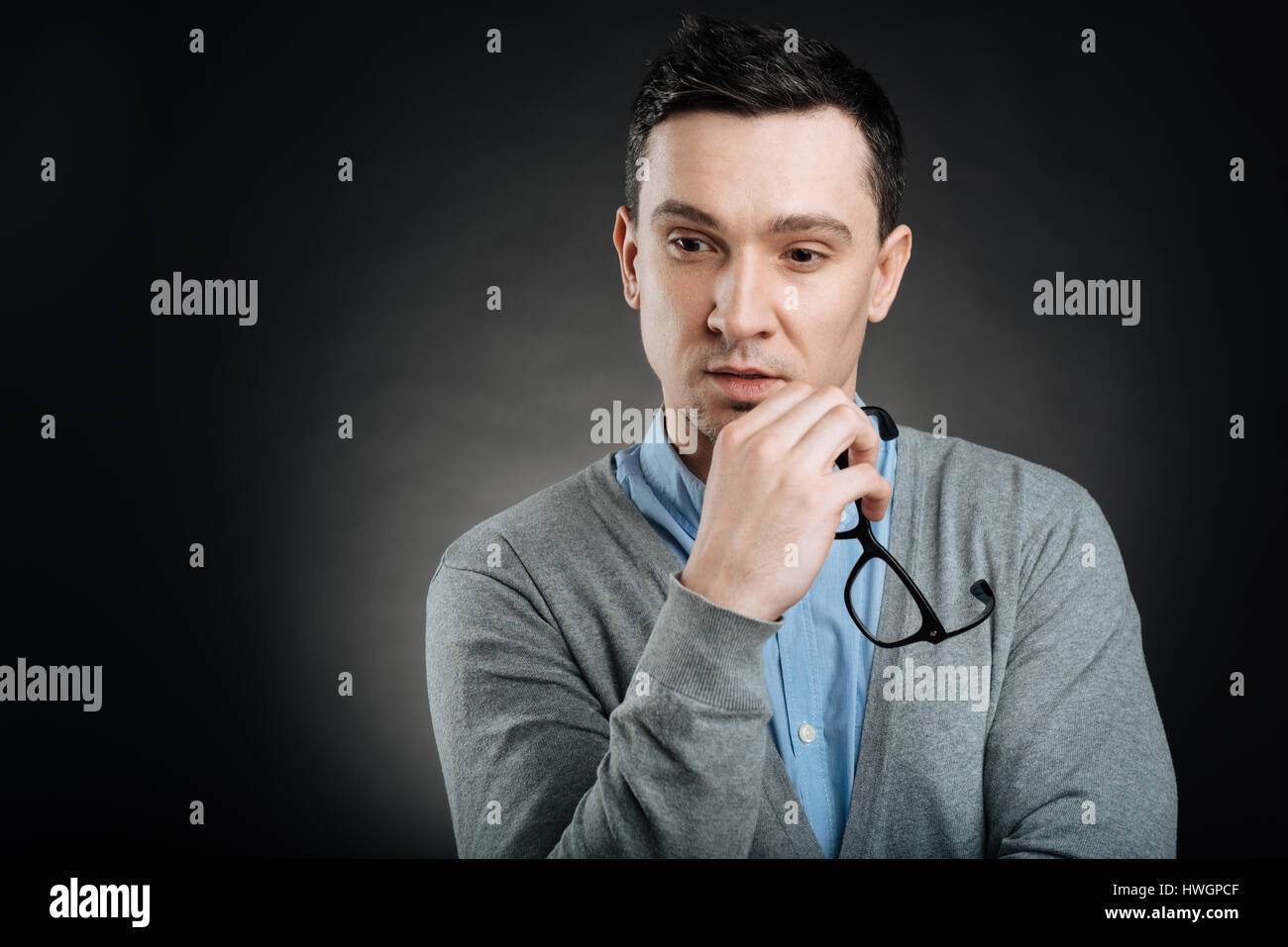 Pensive man keeping glasses in right hand - Stock Image