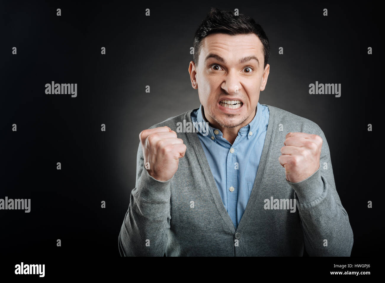 Irritated male person making fists - Stock Image