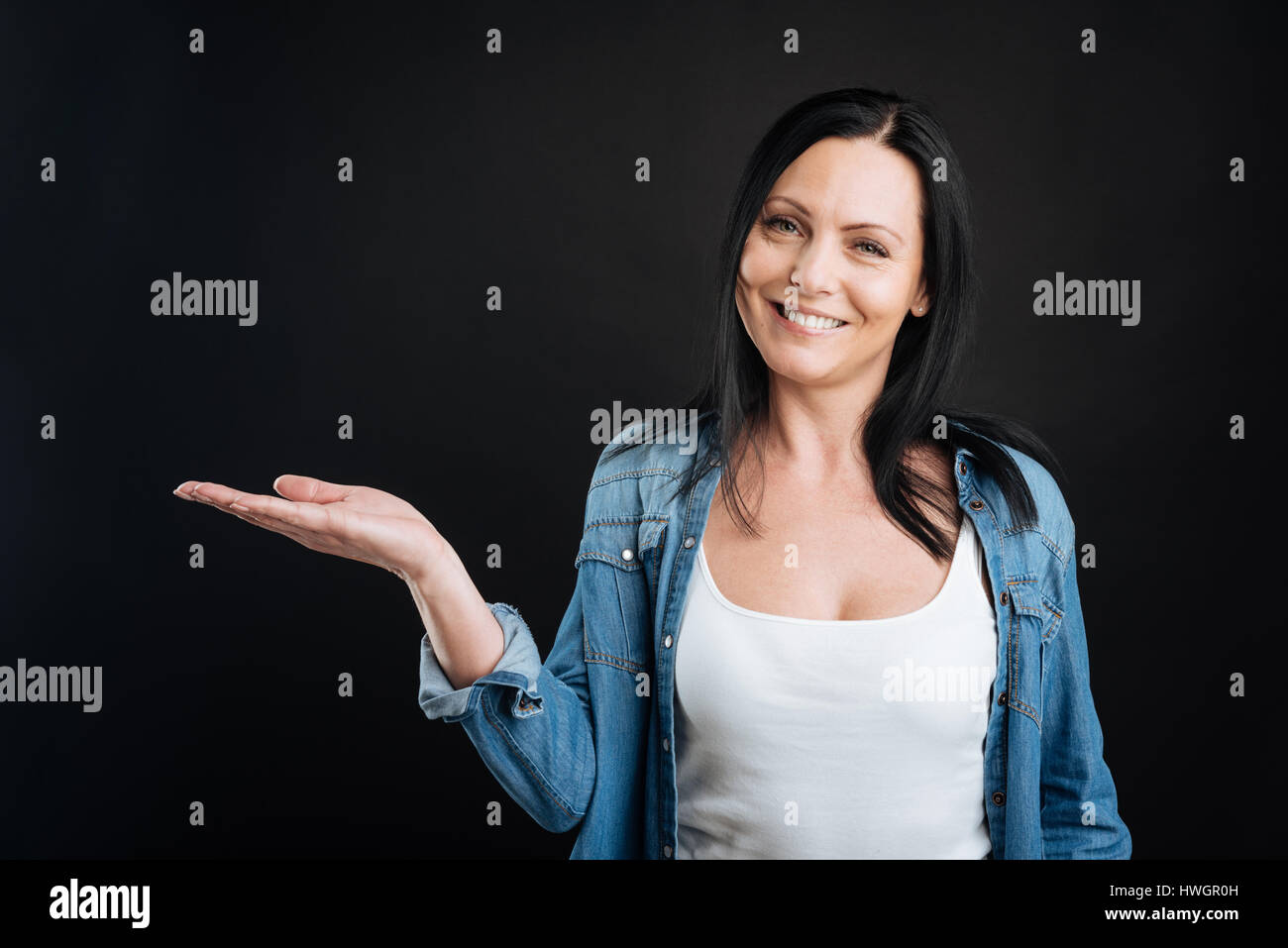 Attractive female keeping her palm of right hand up - Stock Image