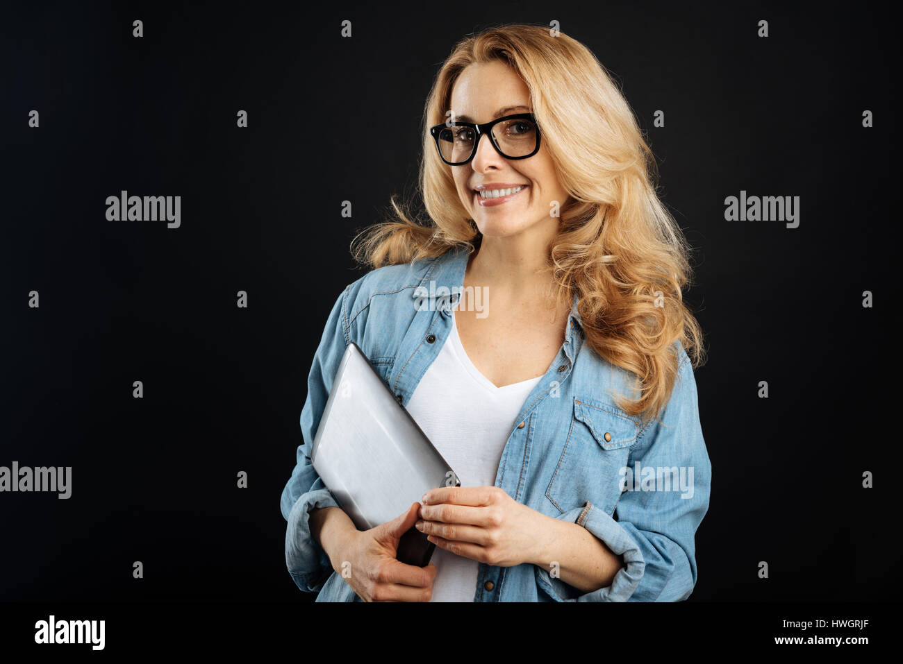 Delighted blonde keeping device in right hand - Stock Image