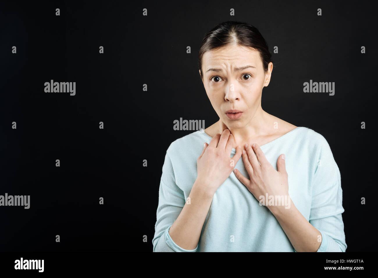 Surprised woman keeping her eyes wide opened - Stock Image