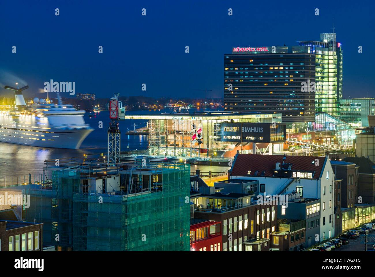 Netherlands, Amsterdam, Eastern Docklands, elevated port view with Muziekgebouw/Bimhuis concert hall, dusk - Stock Image