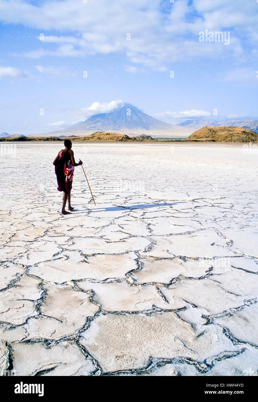 Maasai varrier walking on the dired-out soda-lake called Lake Natron in northern Tanzania.  In the background is Stock Photo