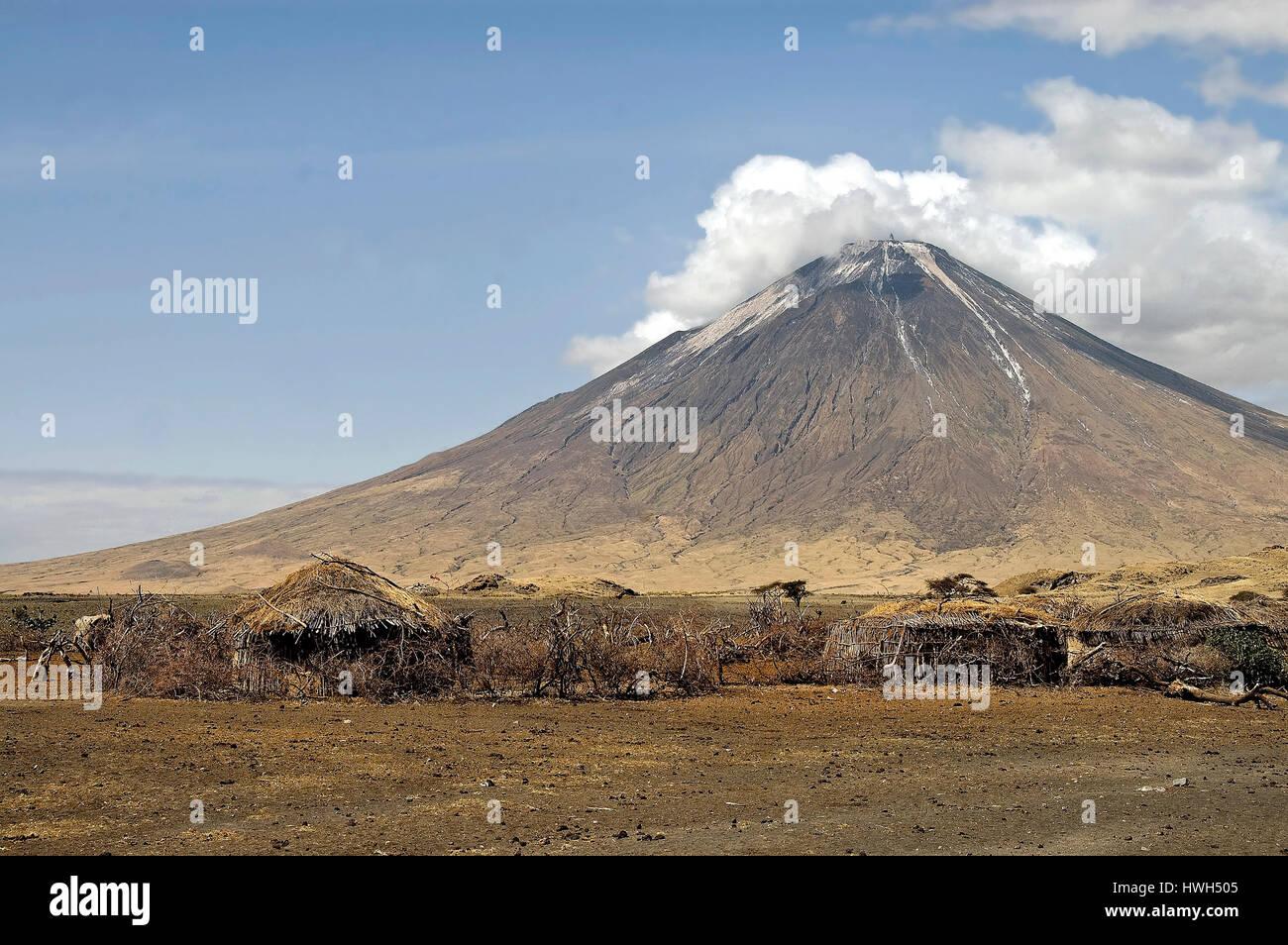 Maasai Village at the foot of Mountain of God (Ol Doinyo Lengai) - the Maasai's holy mountain at Lake Natron, northern Stock Photo