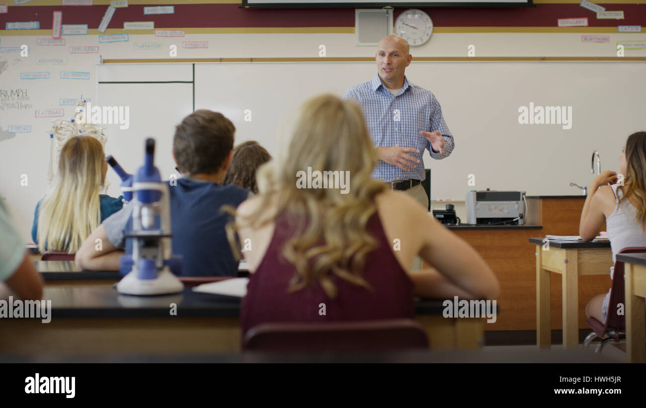 Selective focus view of teacher instructing students in science lab classroom - Stock Image