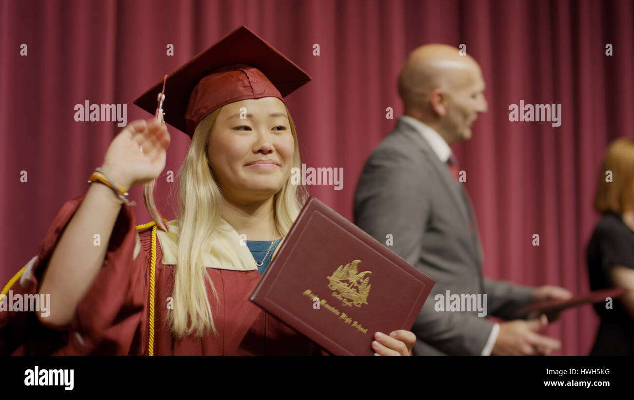 Blurred view of waving student holding diploma on stage during graduation ceremony - Stock Image