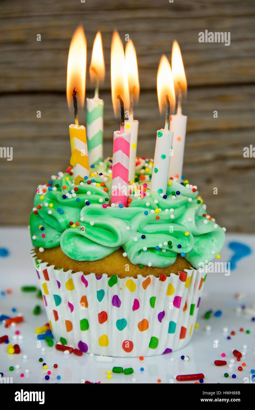 Flaming Birthday Candles In Green Frosting On Cupcake With Sprinkles