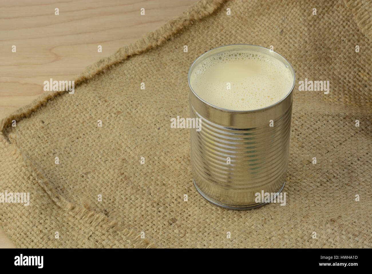 Canned evaporated milk in open can on burlap - Stock Image