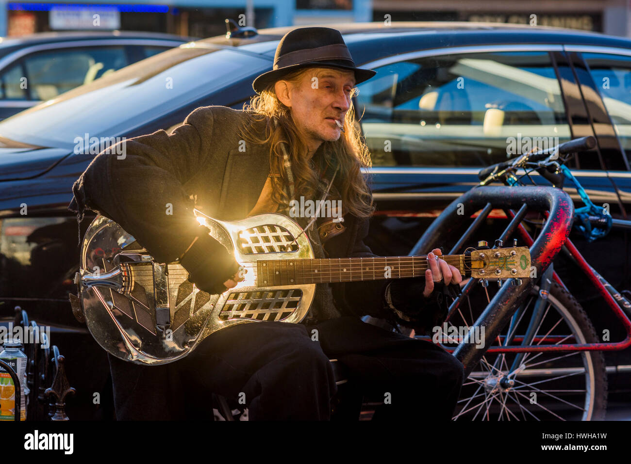 Busker playing slide guitar, Commercial Drive, Vancouver, British Columbia, Canada. - Stock Image