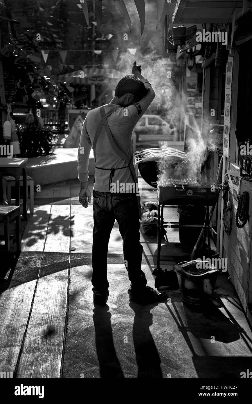 Thailand back street scene with a man cooking a BBQ meal amidst the heat and smoke. Monotone contre jour, black - Stock Image