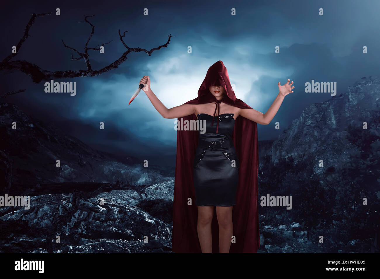 Scary portrait of an asian witch woman covering his face holding a sharp knife bathed in the blood Stock Photo