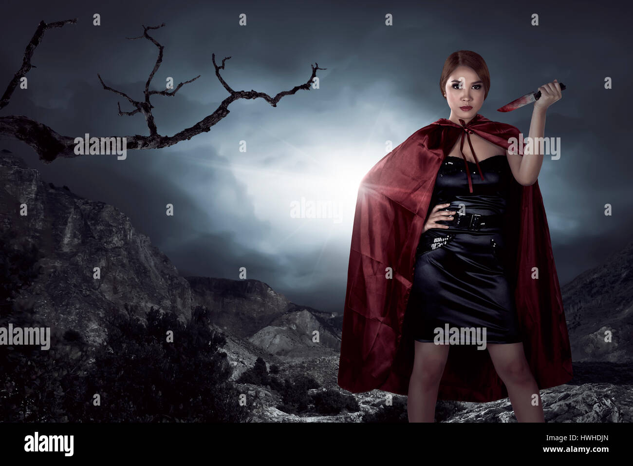 Beautiful asian witch woman holding bloody knife in the night, horror situation. Halloween concept image Stock Photo