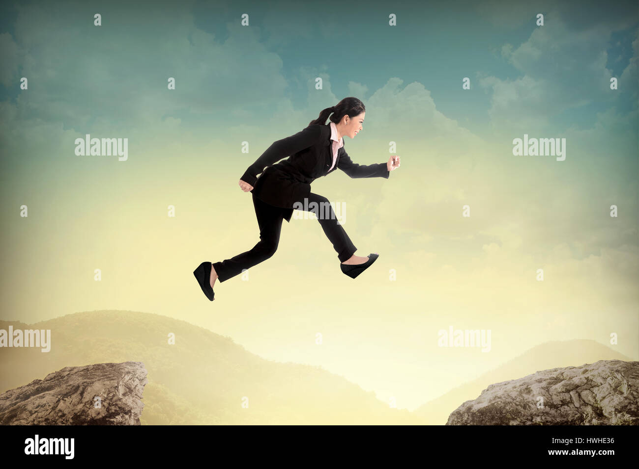 Business woman jump to another peak of mountain  Business