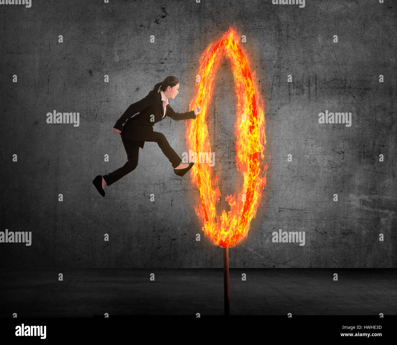 Asian business person jumping through ring of fire. Business risk conceptual - Stock Image