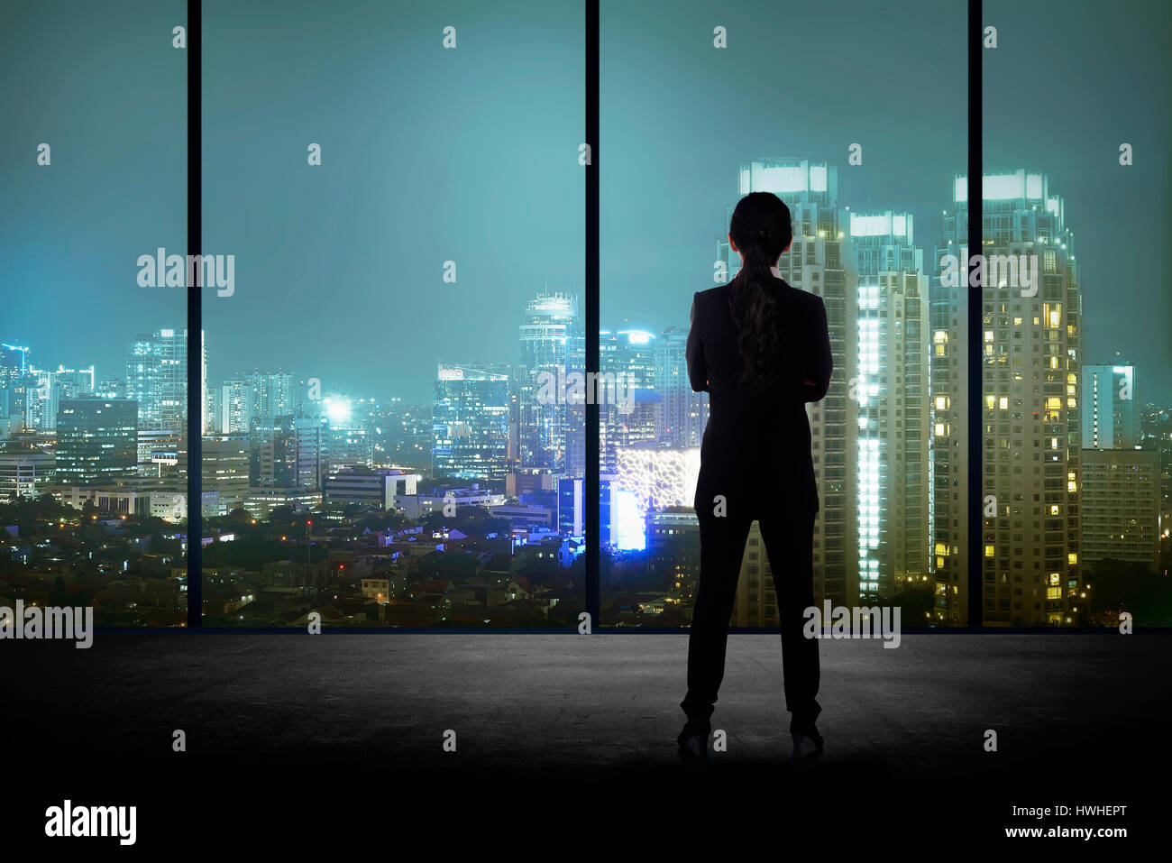 Woman standing in his office looking at the city at night. Business success concept - Stock Image