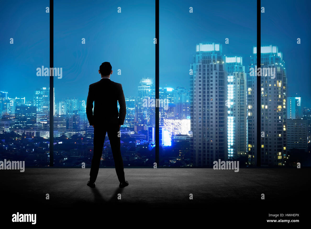 Man standing in his office looking at the city at night. Business success concept - Stock Image
