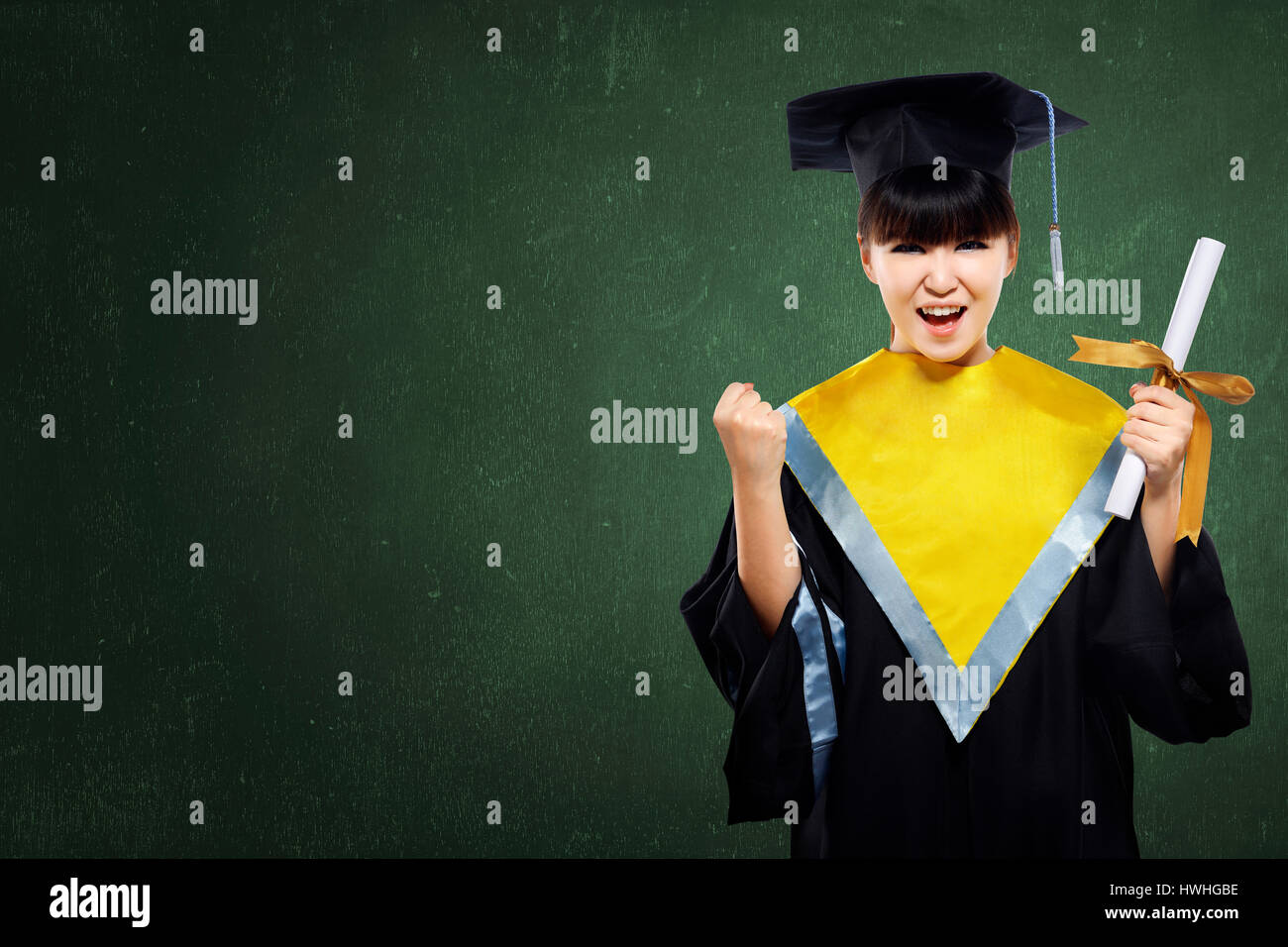 Happy graduated student girl with scroll on green chalkboard background - Stock Image