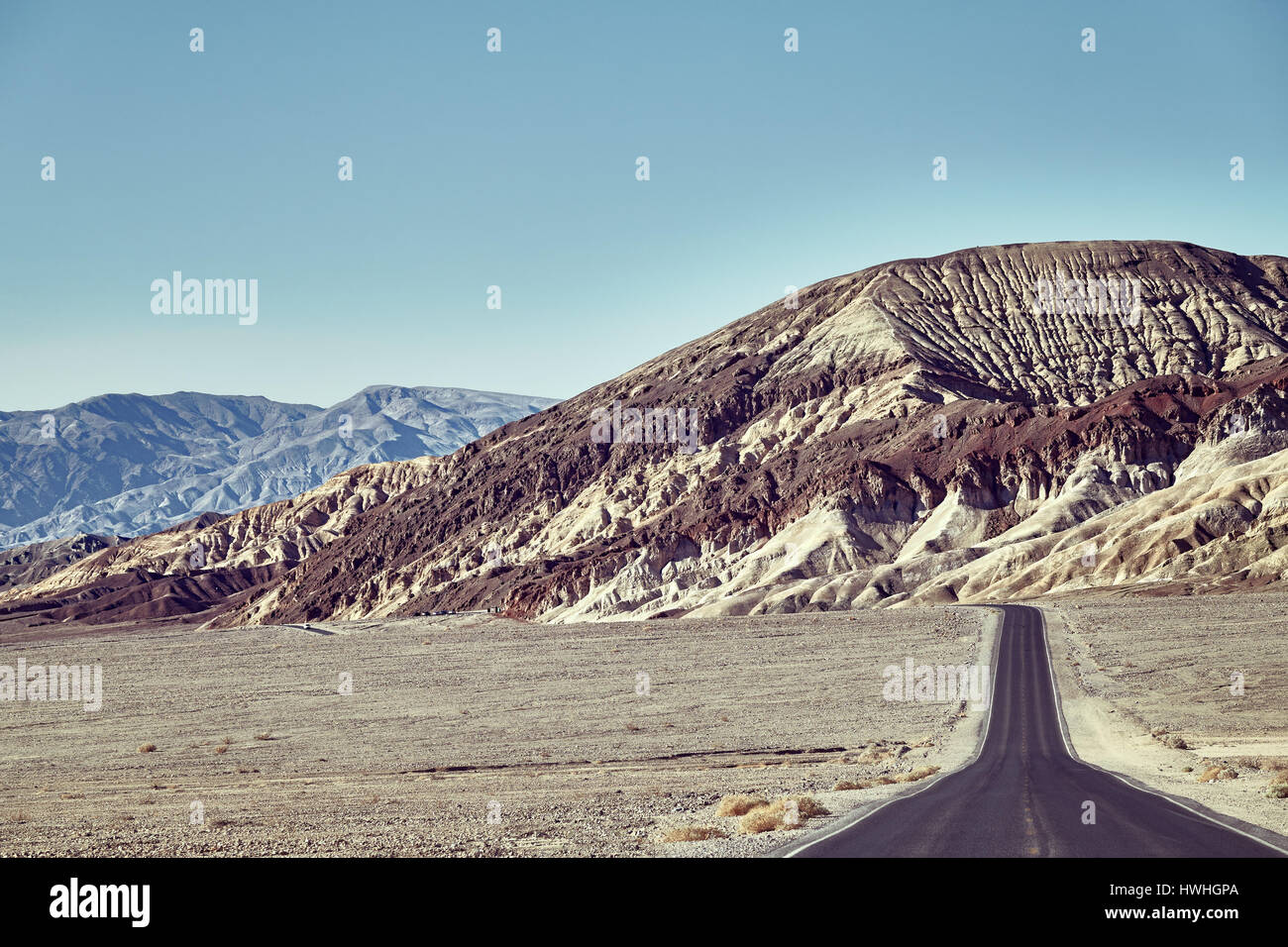 Desert road towards mountain range at Death Valley, color toned image, USA. - Stock Image