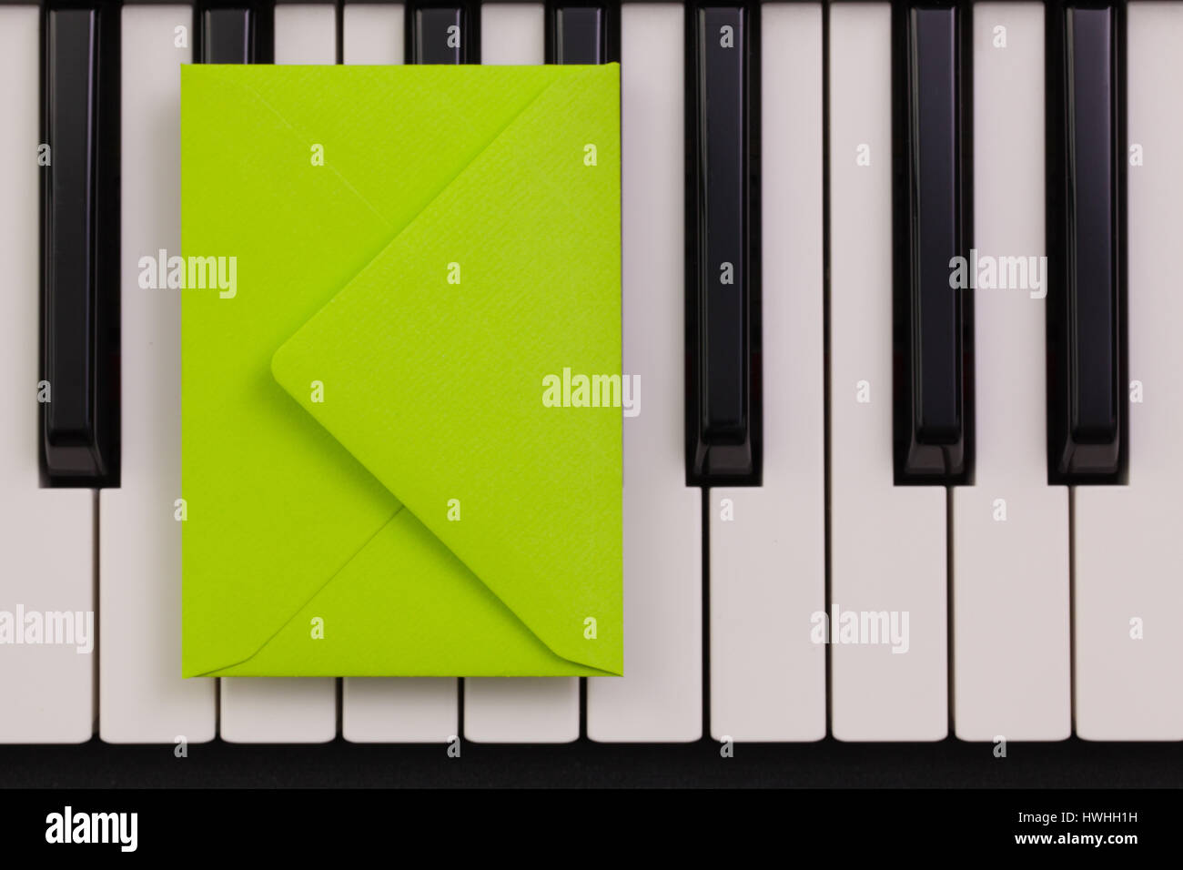 Funny arrangement envelope on the piano keybords - Flat lay image - Stock Image