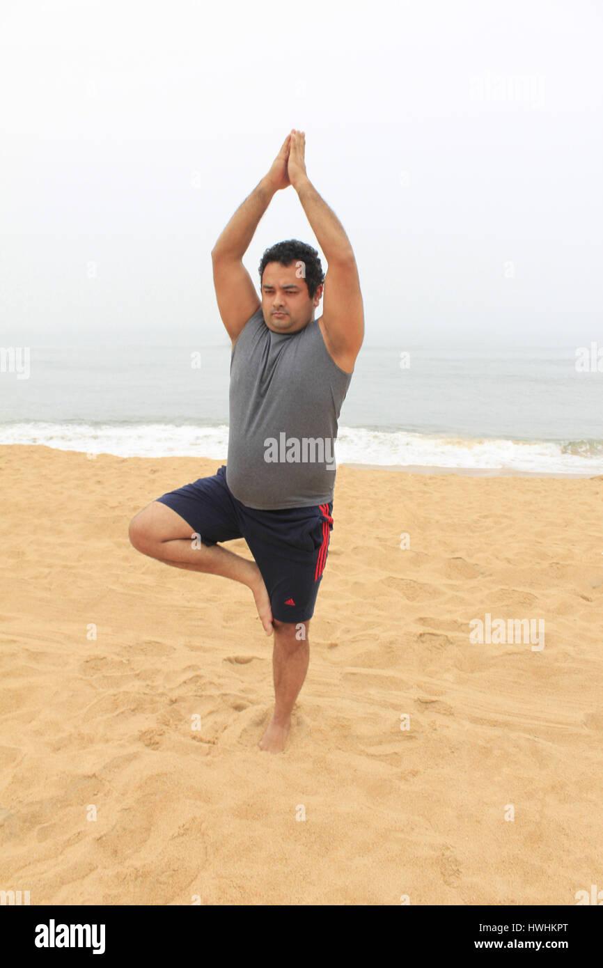 Man in yoga pose Vriksasana, on the beach ,near sea, exercising Stock Photo