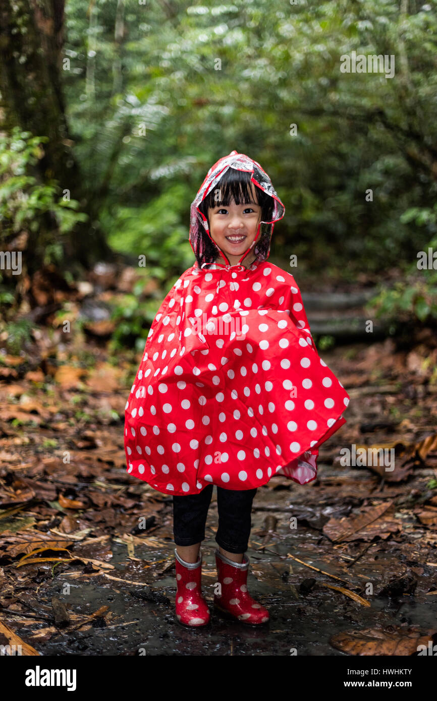 Happy Asian Chinese little girl wearing raincoat in the tropical rain forest alone. - Stock Image