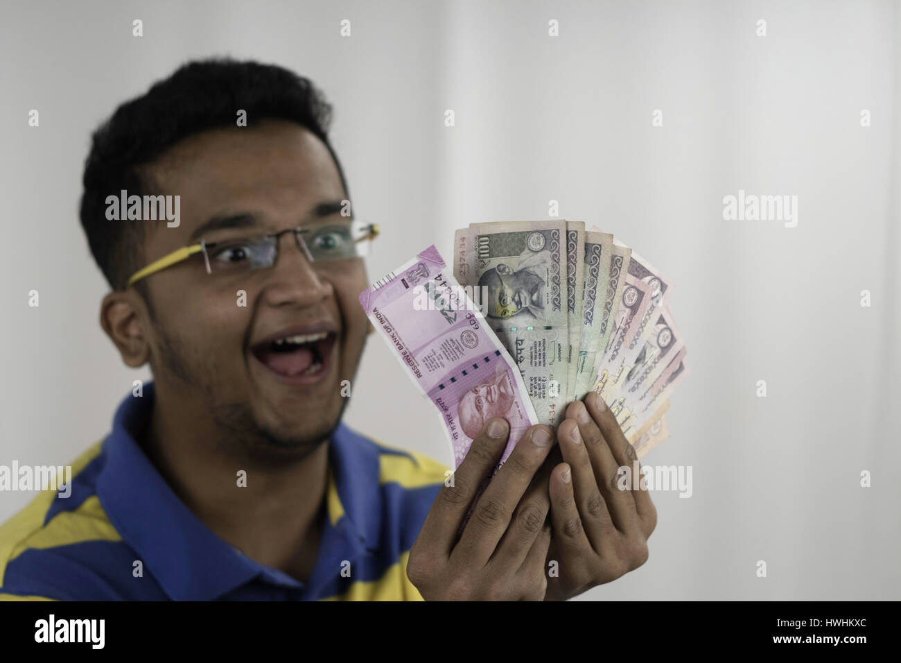 Wide eyed spectacled man going crazy with his money by fanning two thousand , hundred and fifty rupees notes. Post - Stock Image