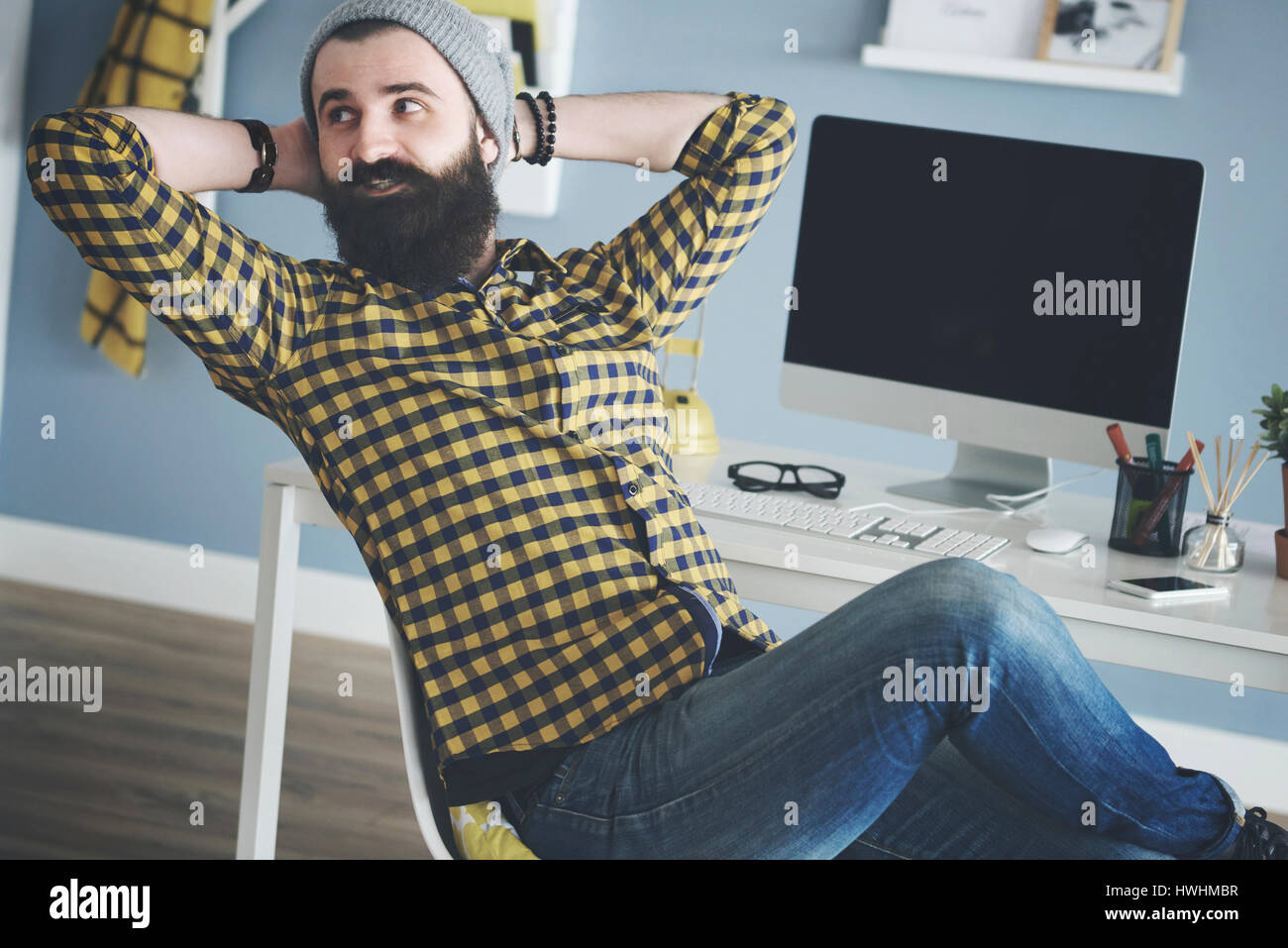 Business man reclining on chair next to computer - Stock Image