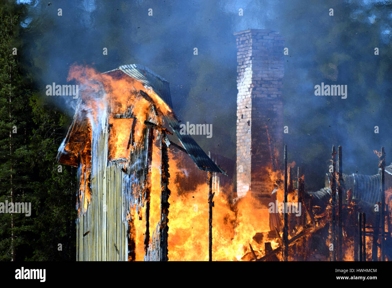 House completely engulfed in flames - Stock Image