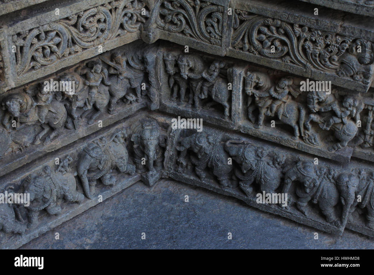Close up of Stone carvings of foliage, warriors , horsemen, elephant procession where two corner wall meet each other on the shrine wall at Chennakesa Stock Photo