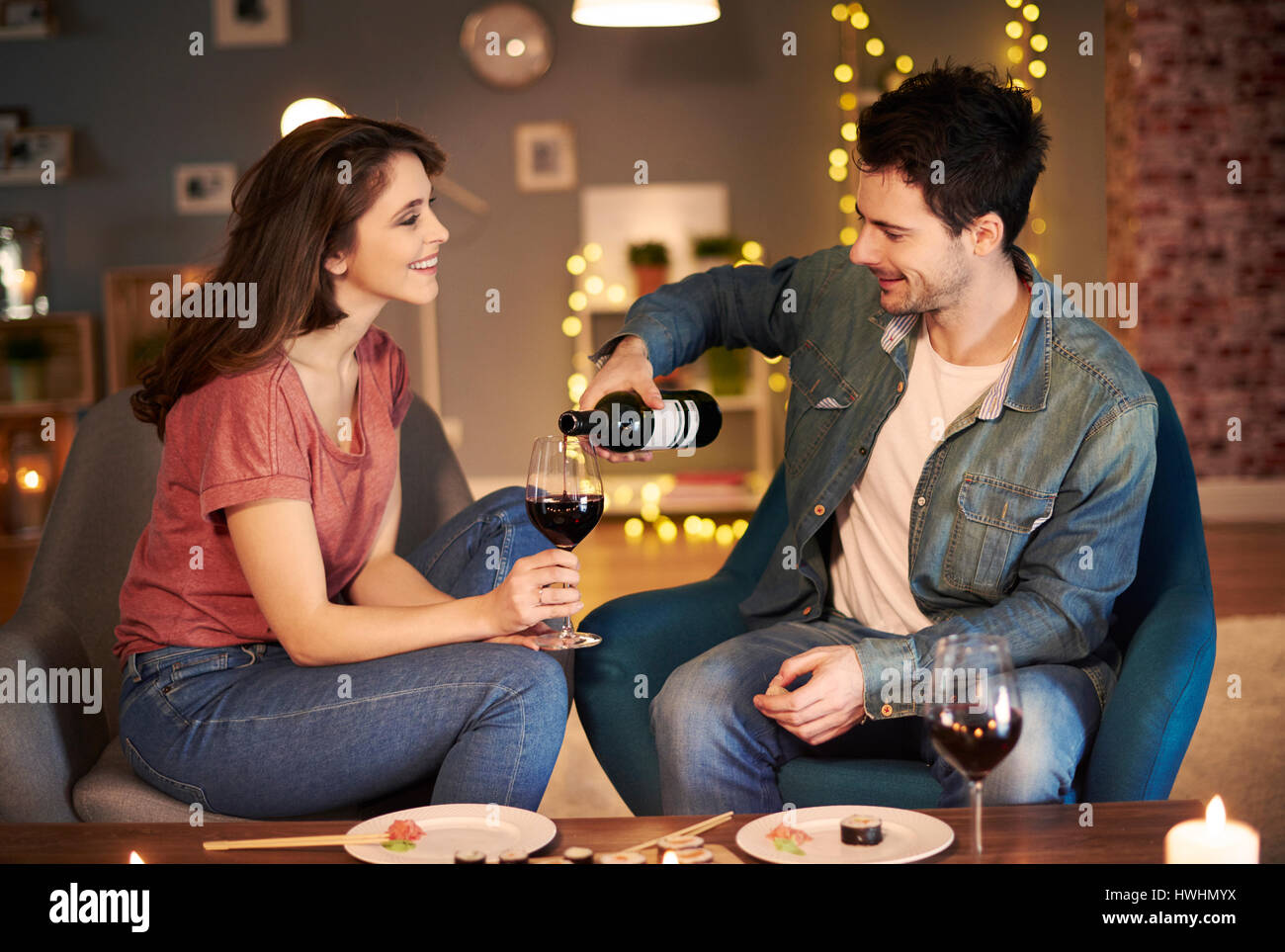 Boyfriend serving red wine while date - Stock Image
