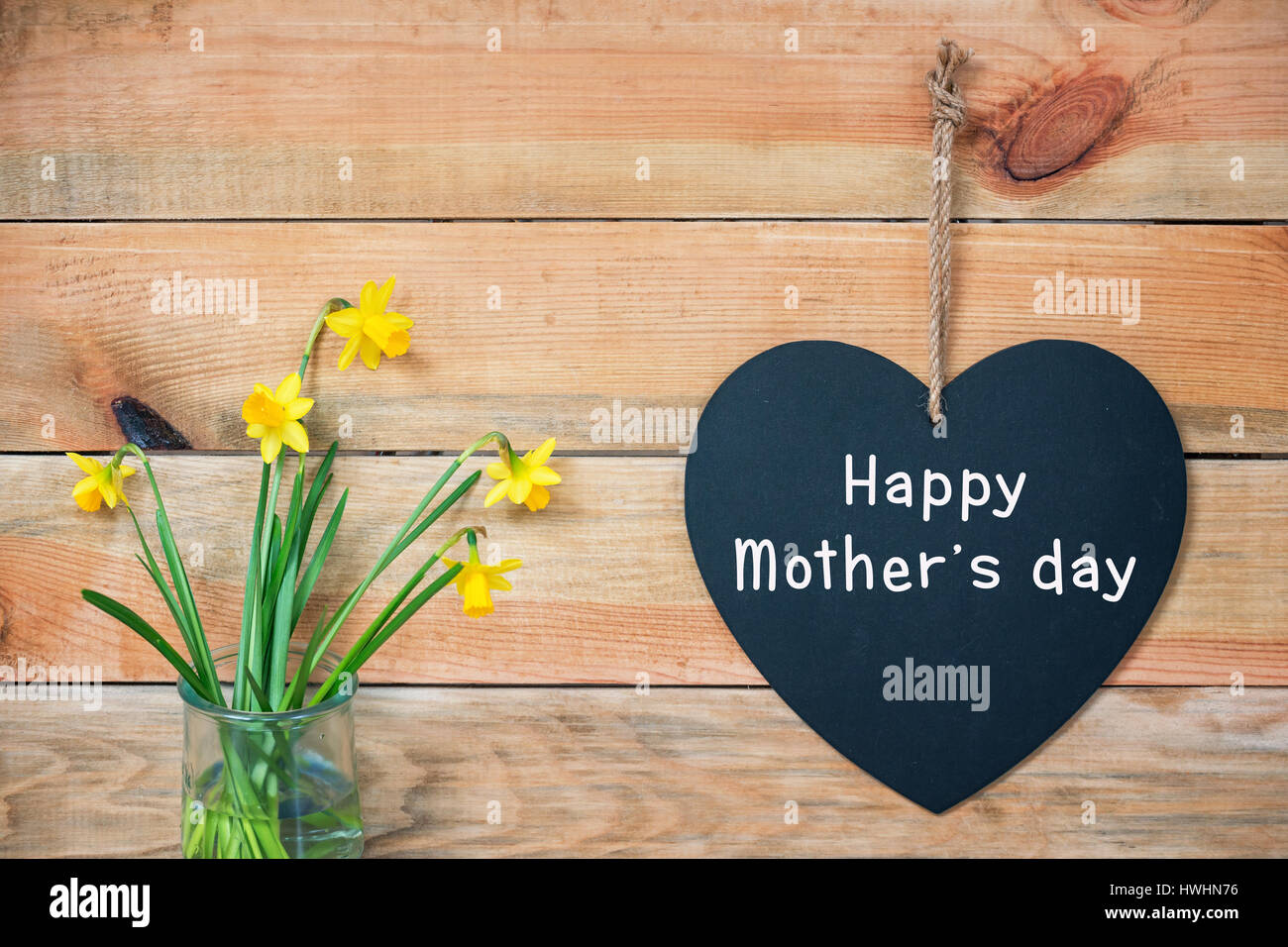 Happy mothers day card, wood planks with daffodils and a blackboard in the shape of a  heart - Stock Image