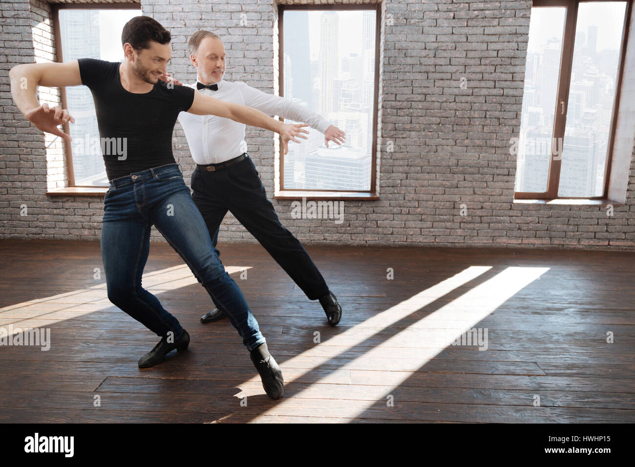 Mastering right dance position of legs. Positive gifted professional dance instructor teaching senior man while - Stock Image