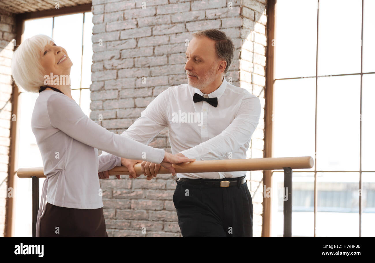 Full of joyfulness. Creative inspired retired couple dancing in the dance studio while expressing joy and standing - Stock Image
