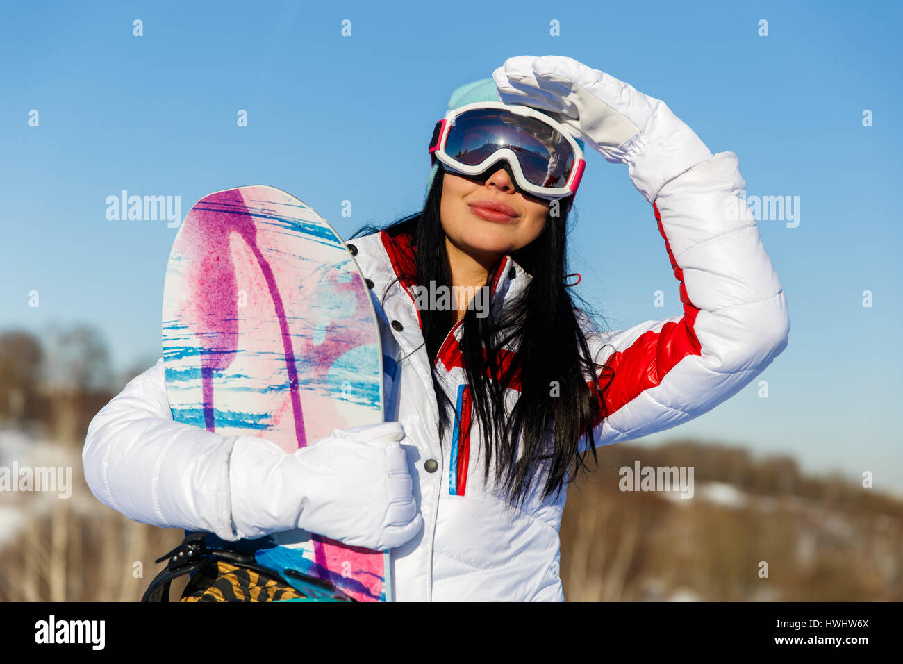 Woman with snowboard and glasses - Stock Image